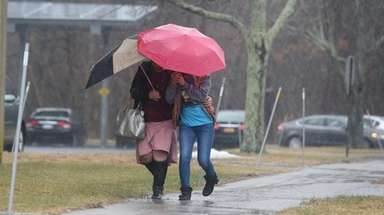 Two women do their best to keep dry