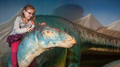 A girl visits with a large, sculpted Edmontosaurus