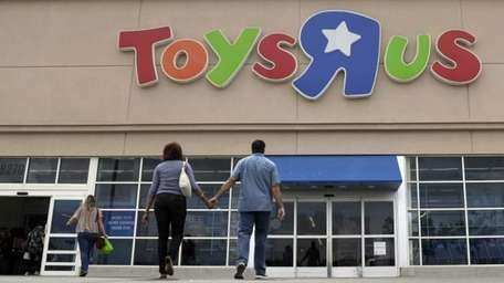 Shoppers walk into a Toys R Us store