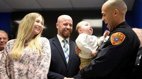 Officer Jon-Erik Negron, holds baby Bryce, as his