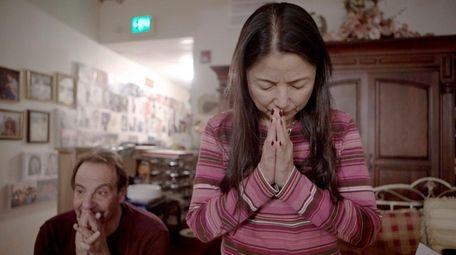 Atsuko Landauer, a volunteer, listens to music at