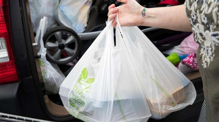 A shopper in Riverhead carries groceries in plastic