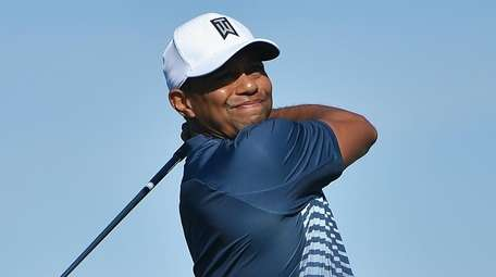 Tiger Woods plays his shot from the 18th