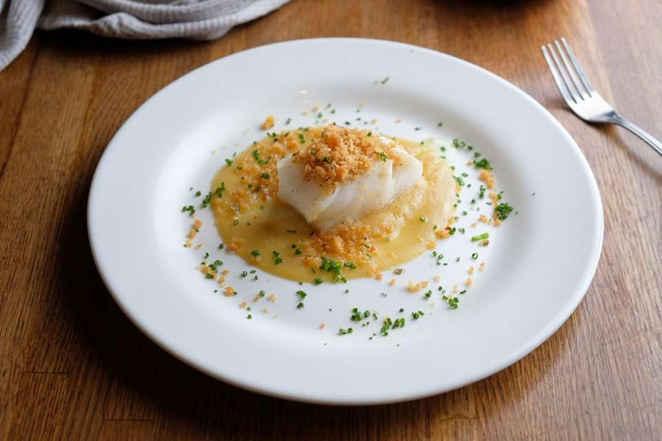 Cod arrives topped with breadcrumbs, seated in a