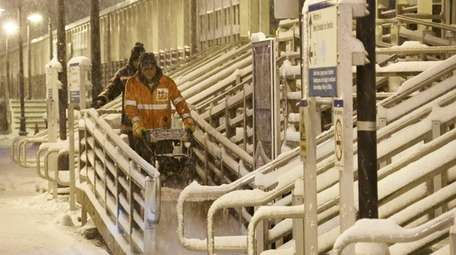 Workers clear snow at the LIRR station in