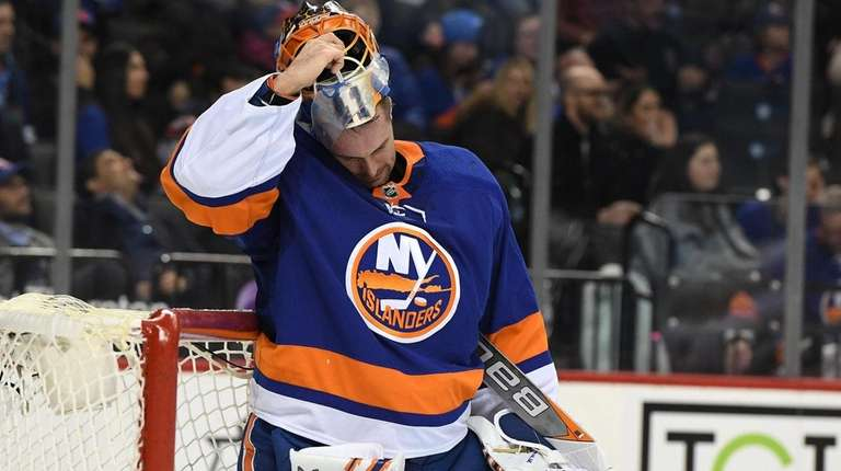 Islanders goaltender Jaroslav Halak removes his mask after