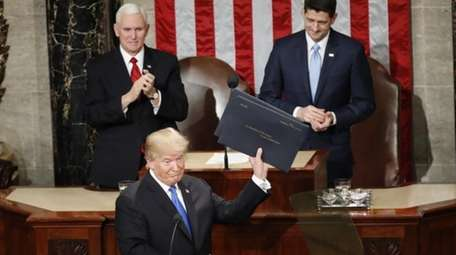 President Donald Trump holds up copies of his