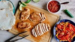 Spice-coated seared chicken breasts and oven-roasted bell peppers,