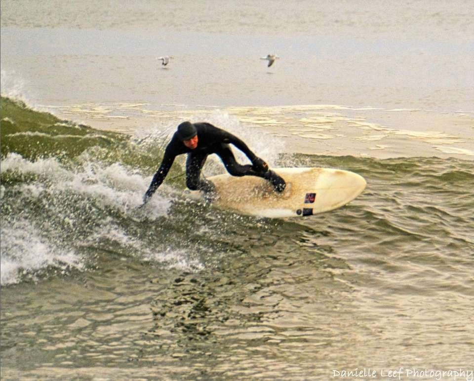 Defying gravity, a surfer at Coopers Beach in
