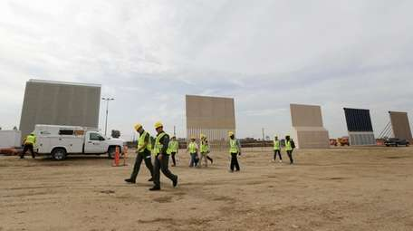 People pass border wall prototypes as they stand