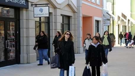 Shoppers walk around Tanger Outlets at the Arches