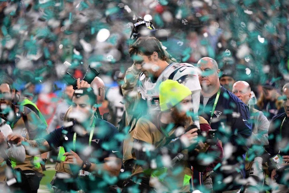 New England Patriots quarterback Tom Brady (C) leaves