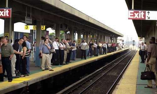 A large crowd of commuters wait for the
