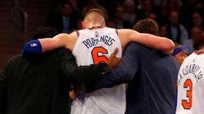 Kristaps Porzingis of the Knicks is helped off