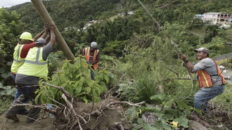 Workers in Puerto Rico work to return electricity.