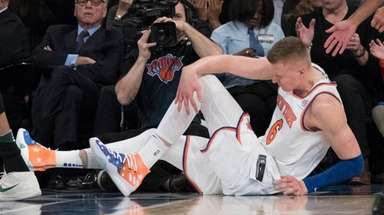 Knicks forward Kristaps Porzingis clutches his left knee