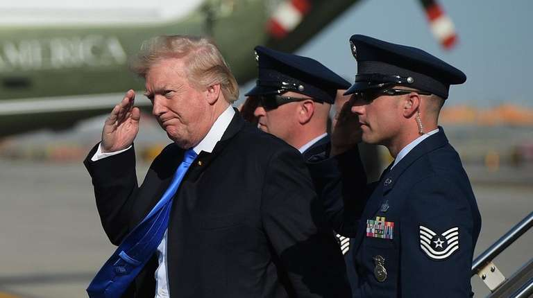 President Donald Trump salutes a military aide upon