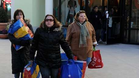 Shoppers walk around Tanger Outlets at the Arches.