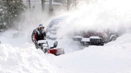Abilio Oliveira uses a snowblower on Barone Drive