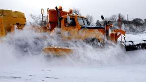 A snowplow makes its way down Sunrise Highway