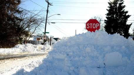 A pile of snow nearly covers a stop