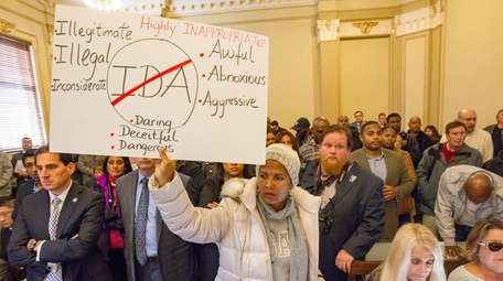 Jinette Frederique holds a sign at a Hempstead