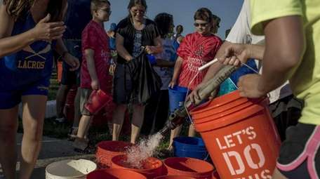 Participants pass each other filled buckets for the