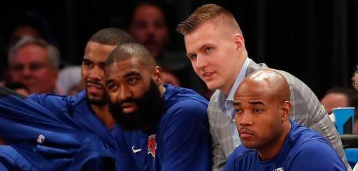 Knicks forward Kristaps Porzingis, center, watches play from