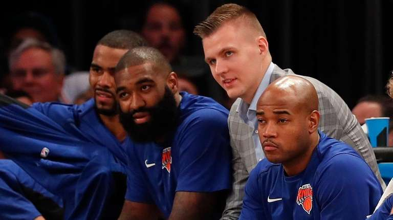 Knicks forward Kristaps Porzingis, center, watches play from