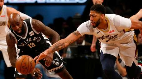 Quincy Acy of the Nets battles for a