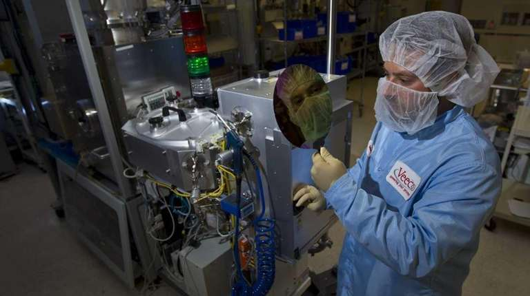 A mechanical engineer holds a data wafer near