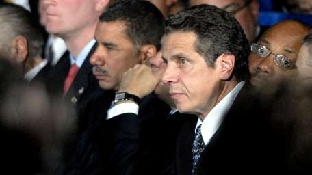 NY Attorney General Andrew Cuomo, right, sits near