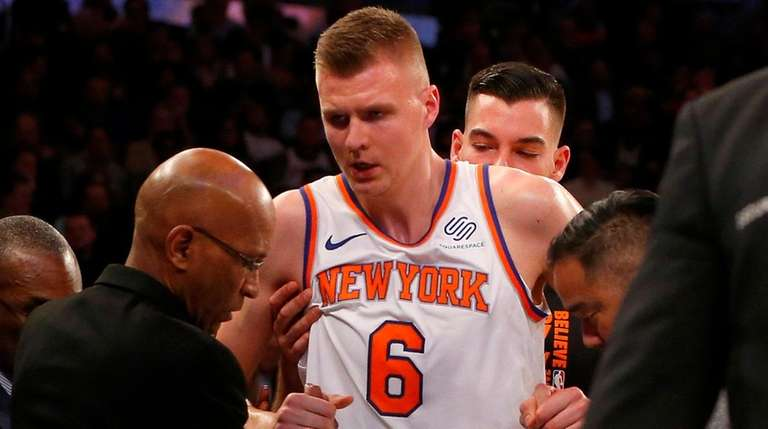 Knicks forward Kristaps Porzingis is helped off the