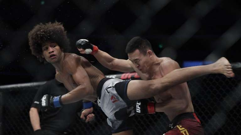 Alex Caceres (left) fights Guan Wang during UFC