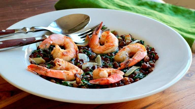Seared shrimp atop simmered lentils with baby arugula.