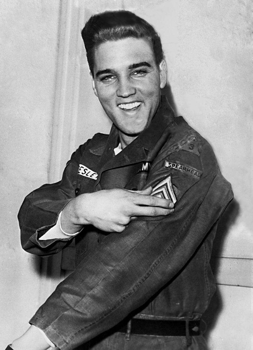 Elvis Presley smiles after he is promoted to