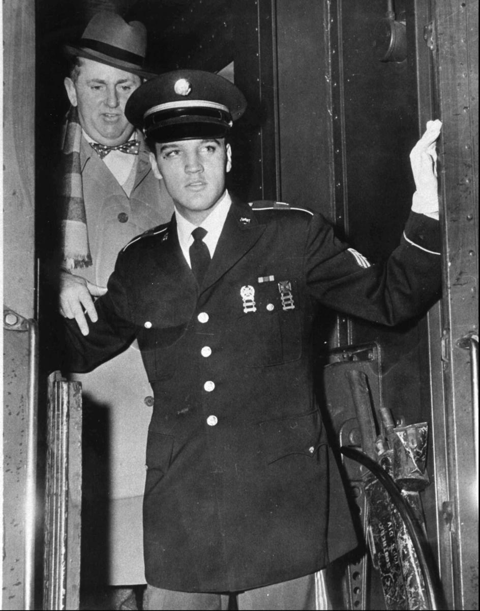 Elvis Presley and Col. Tom Parker step off