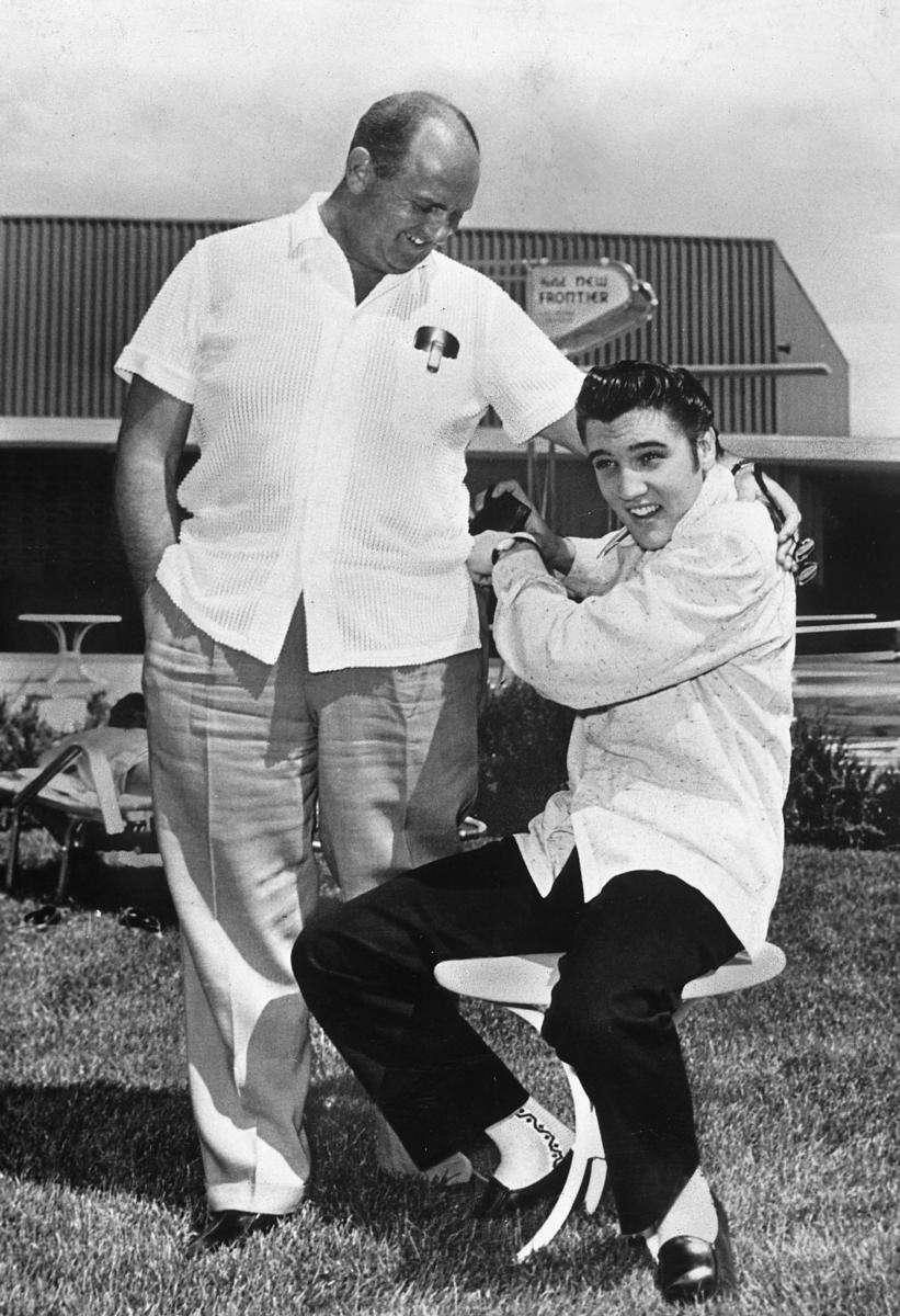Elvis Presley grabbing a wallet from manager Col.