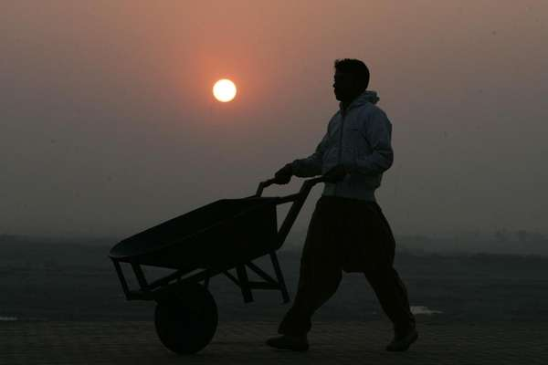 A sunset silhouettes a man with a hand