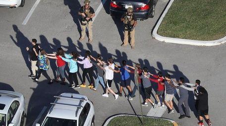 People leave Marjory Stoneman Douglas High School after