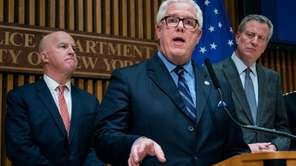 NYPD Deputy Commissioner John Miller, flanked by Police