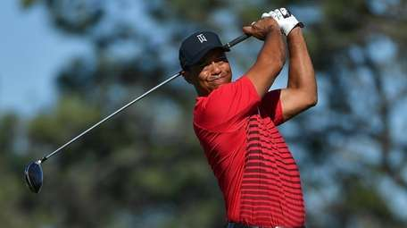 Tiger Woods plays his shot from the tee