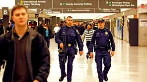 Police officers patrol the baggage claim area at