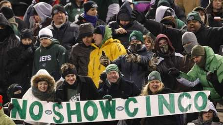 New York Jets fans hold a sign referring