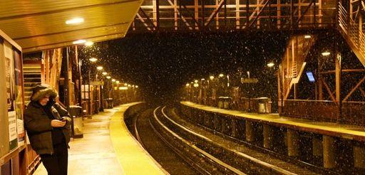 A man waits for his train as snow