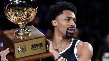 The Nets' Spencer Dinwiddie holds up his trophy