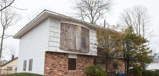 Plywood covers the windows of an abandoned home