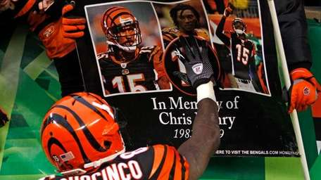 Chad Ochocinco touches a sign honoring teammate Chris