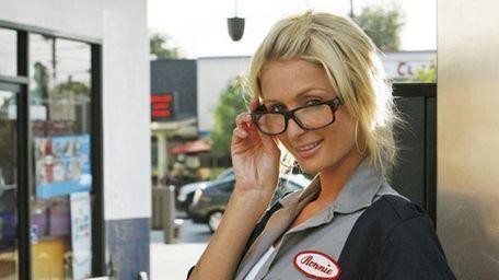 Paris Hilton poses as a gas station attendant