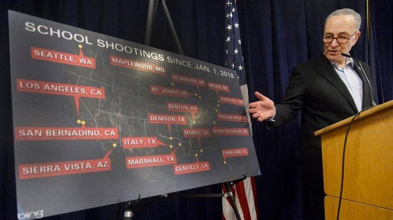 Sen. Chuck Schumer displays a poster showing